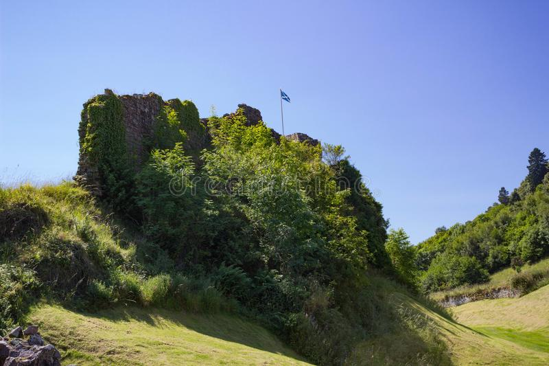 A section of the Urquhart Castle Ruins with Scottish Flag. A section of the Urquhart Castle Ruins brightly illuminated by the sun with the Scottish Flag flying royalty free stock photography