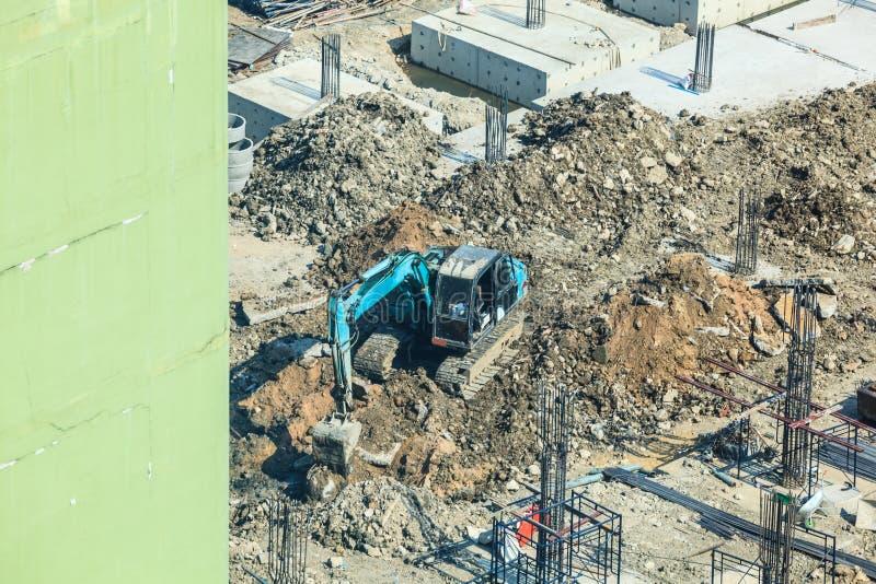 Sector de la construcción, sitio de la construcción de edificios concretos Pilas concretas conducidas en la tierra por el excavad foto de archivo libre de regalías
