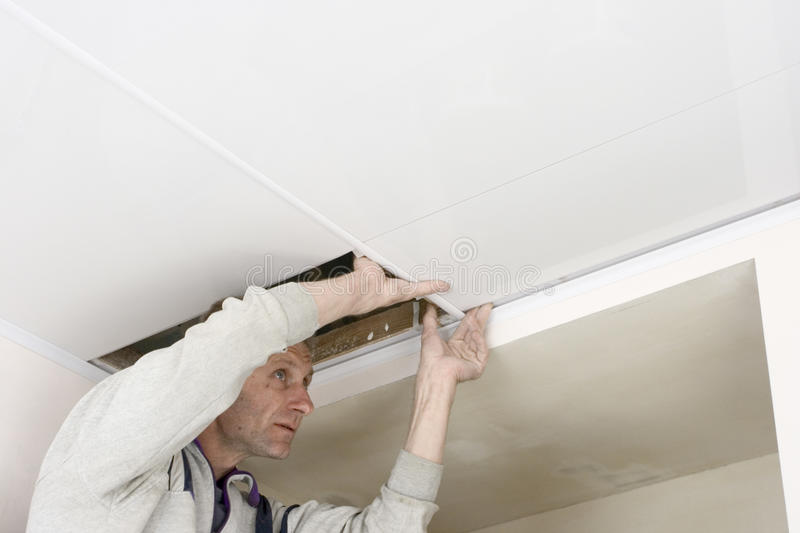 Sectoring. Installation plastic batten on ceiling stock photos