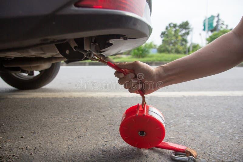 Secuencia común de la cuerda del hombre mecánico en el coche a tirar de nuevo al garaje para la reparación de fijación después de fotos de archivo libres de regalías