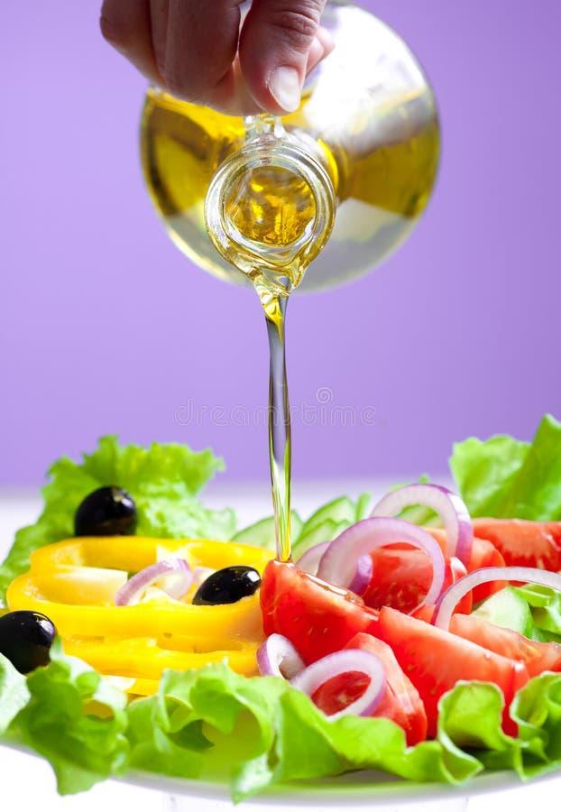 Secuencia del aceite de oliva y ensalada sana de las verduras frescas fotografía de archivo