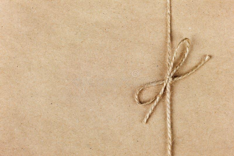 Secuencia o guita atada en un arco en el papel de Kraft fotos de archivo