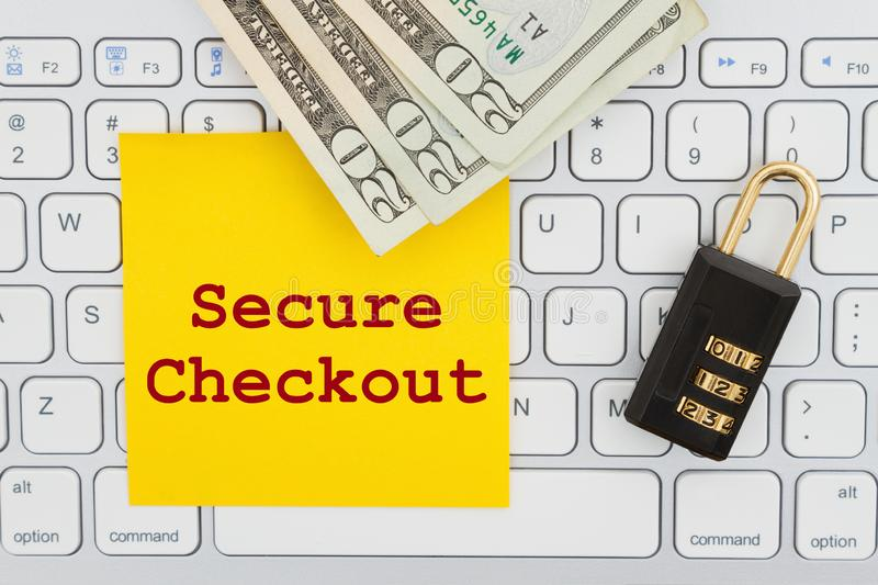 Secure Checkout with combination lock and money on a keyboard with sticky note. Secure Checkout with combination lock and money on a computer keyboard with stock image