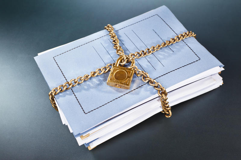 Secure file. Stack of files and folder being surrounded by locked chain royalty free stock images