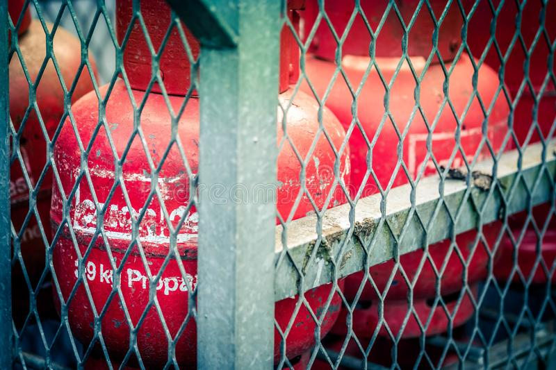 Secured red bottled gas cannisters in the UK. March 2019 - United Kingdom: Some bottled LPG gas is secured in a cage at a fuelling station in the UK safetly stock images