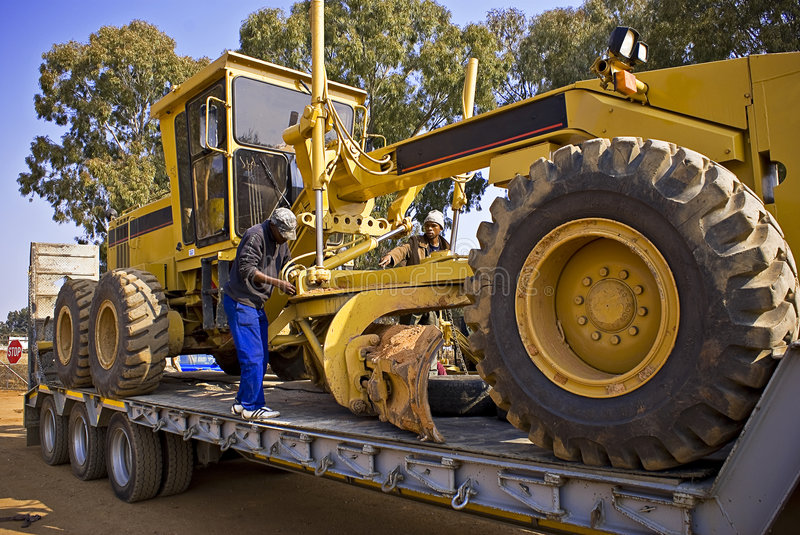 Securing Chain Fastener 02. Heavy Duty Construction Equipment. Team of laborers secure chain strapping to ready the grader during road transport to it's new royalty free stock photo