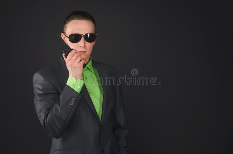 Security. Security agent man is talking on the portable radio station and intently looking isolated on black background. Need assistance royalty free stock images