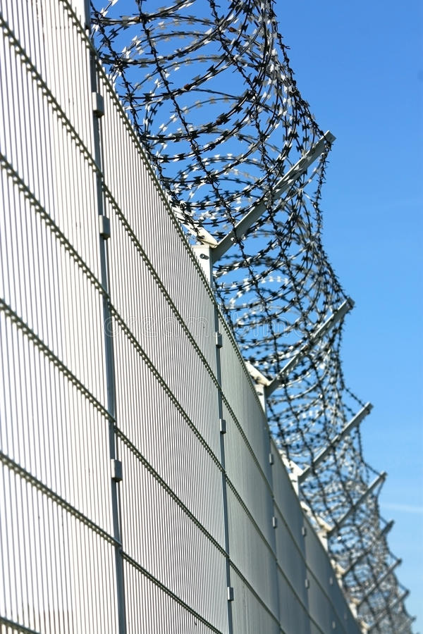 Security barbed fence. Security white barbed fence and sky royalty free stock photos