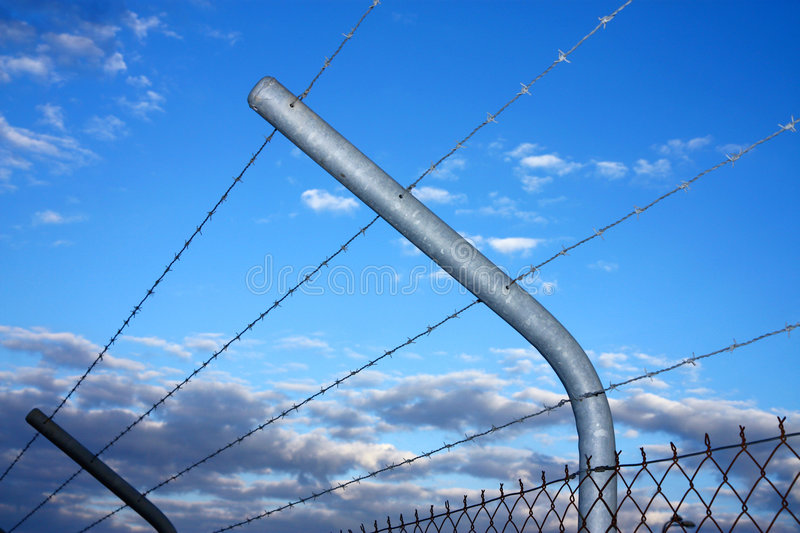 Security barbed wire fence. During sunset stock photography