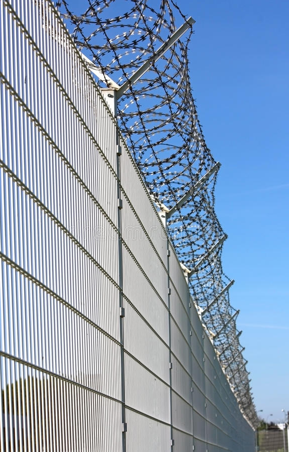 Security boundary barbed fence. Security boundary barbed white fence stock photo