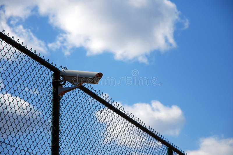 Security camera on fence. Security camera mounted on top of chain link fence against blue skies on sunny day stock image