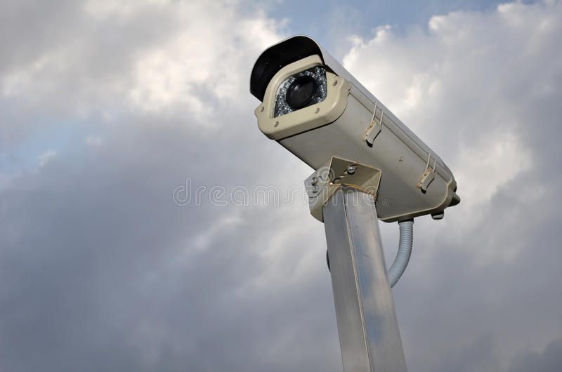 Security camera against a cloudy sky. Security concept stock photography