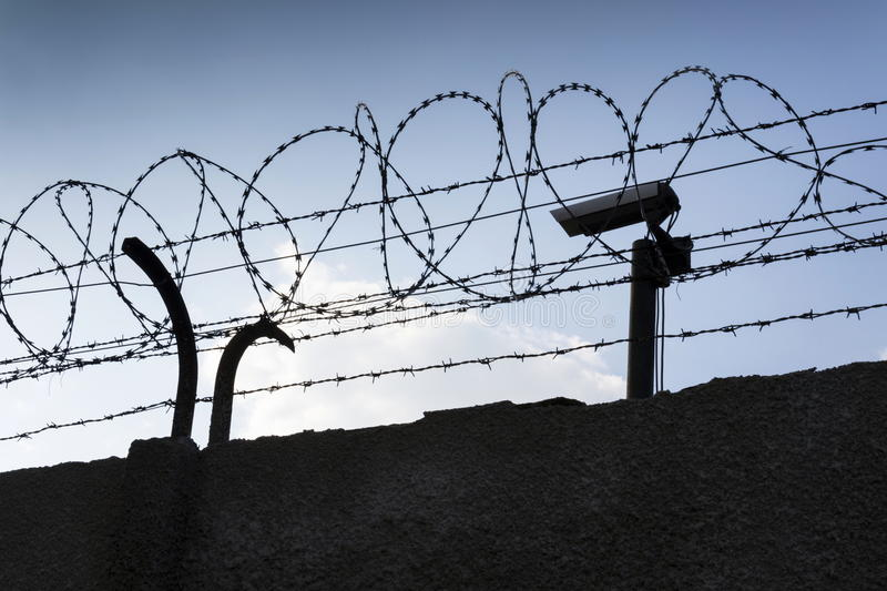 Security camera behind barbed wire fence around prison walls. Security camera behind barbed wire fence stretched around prison walls royalty free stock photography