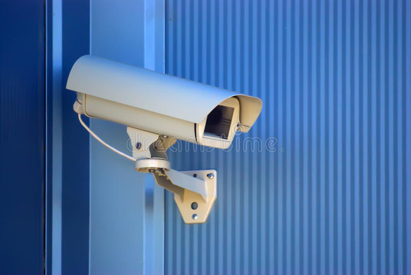 Security camera. On the blue wall stock photos