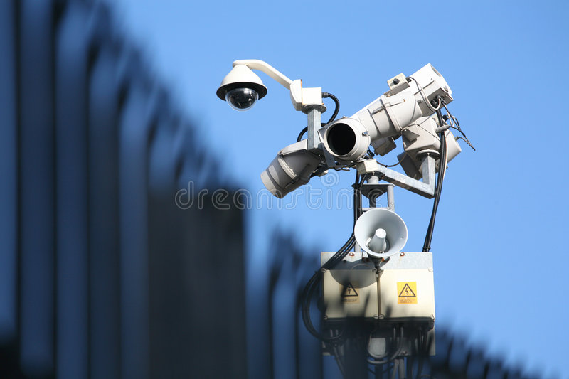 Security Camera, Light & Fence. High-tech security monitoring with soft-focus palisade fencing in foreground