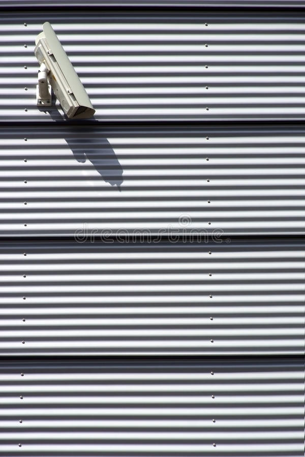 Security Camera. The photograph of a modern house facade made of corrugated sheet metal with an installed security camera stock photos
