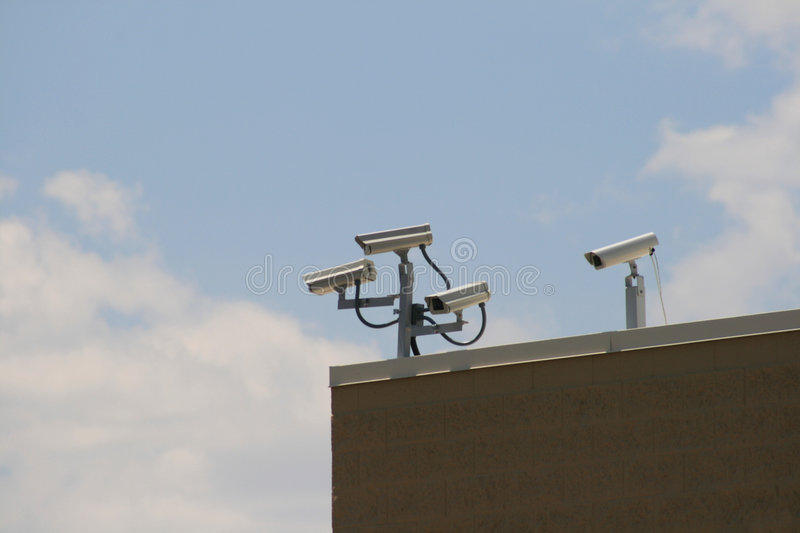 Security cameras. Multiple security cameras record from the corner of a building stock image