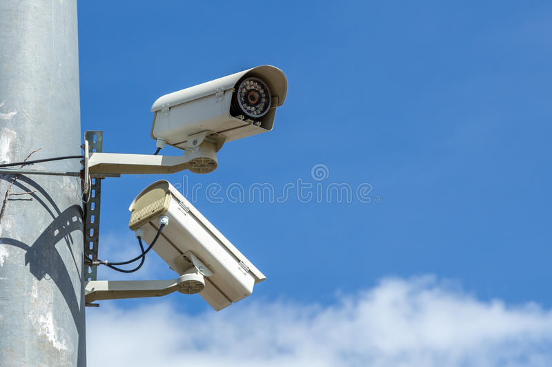 Security cameras with blue sky. Security cameras with pole under blue sky royalty free stock images