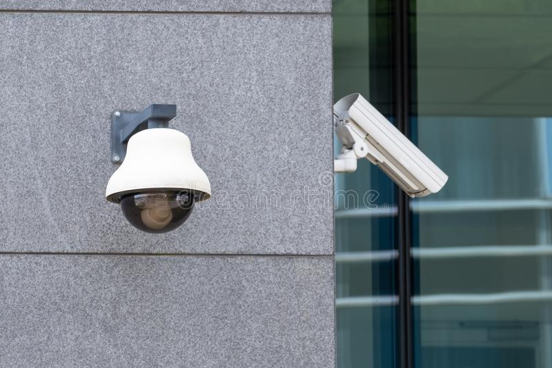 Suveillance cameras on facade. Security cameras, one with dome, on an office building external wall stock images