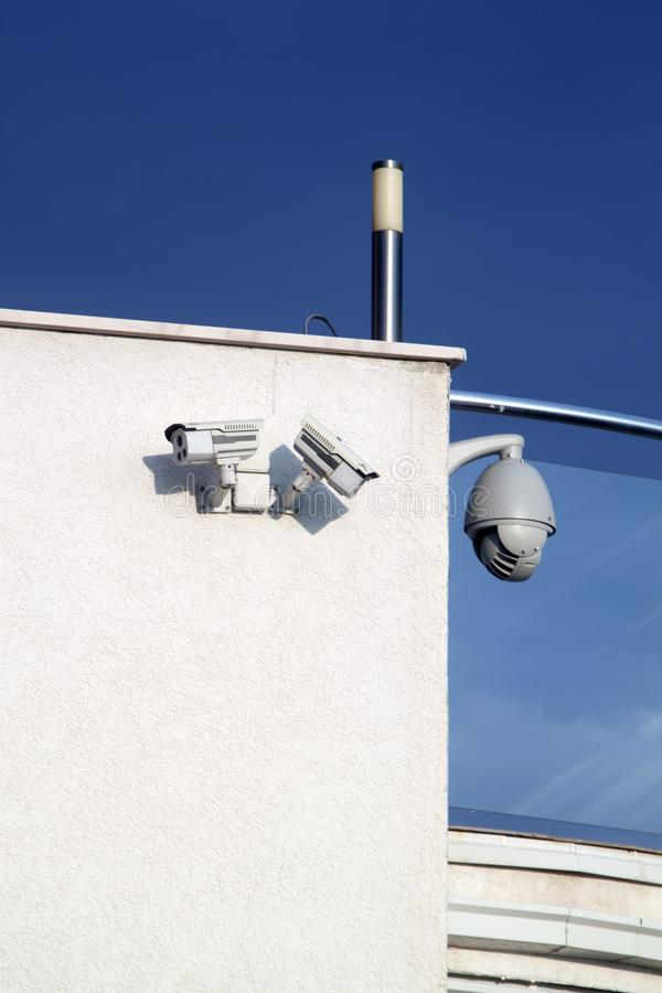 Security cameras on the wall with copy space. Surveillance, cctv, video, building, system, white, watching, safety, suspicious, monitoring, spy, technology royalty free stock image