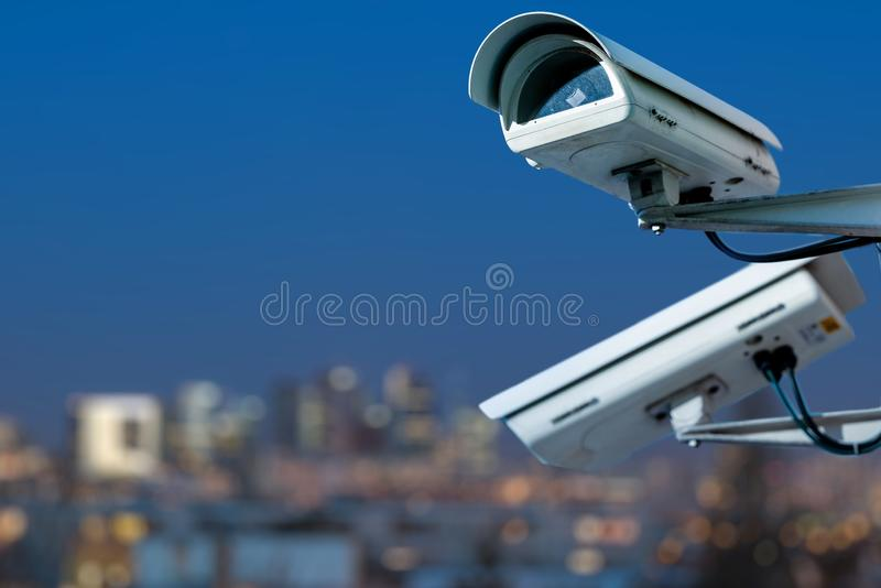 Security CCTV camera monitoring system with panoramic view of a city on blurry background. Focus on security CCTV camera monitoring system with panoramic view of stock photo