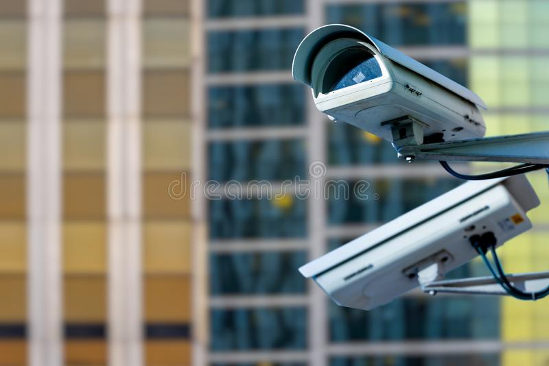 Security CCTV camera or surveillance system with buildings on blurry background. Focus on security CCTV camera or surveillance system with buildings on blurry stock image