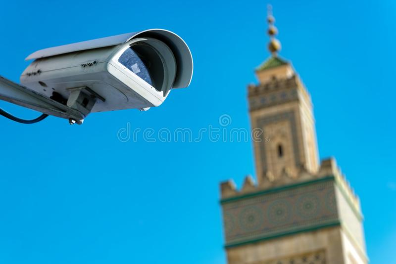 Security CCTV camera or surveillance system with mosque on blurry background. Focus on security CCTV camera or surveillance system with mosque on blurry stock image