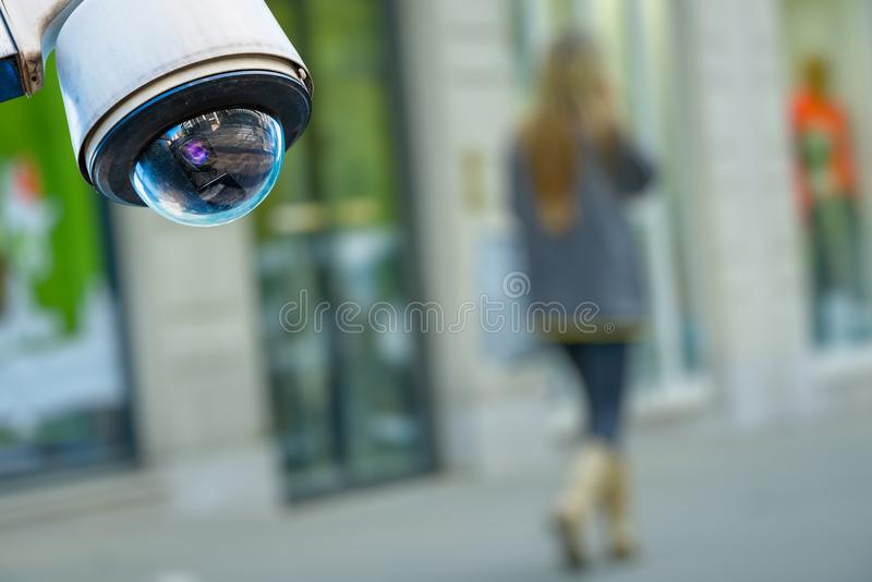 Security CCTV camera or surveillance system with a pedestrian on blurry background stock images
