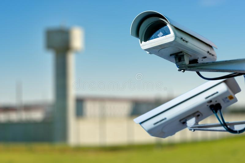 Security CCTV camera or surveillance system with prison on blurry background. Focus on security CCTV camera or surveillance system with prison on blurry stock image