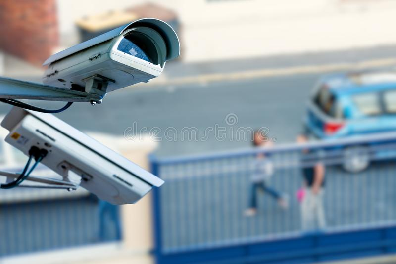 Security CCTV camera or surveillance system with street on blurry background. Closeup on security CCTV camera or surveillance system with street on blurry stock image