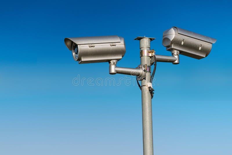 Security CCTV video camera against blue sky. stock photo