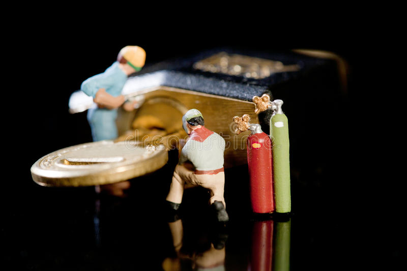 Security Check And Maintenance. Miniature model workmen with power tools and acetylene torch conduct an inspection and maintenance on a padlock and key royalty free stock photos