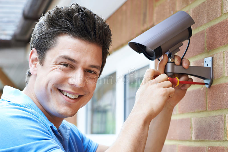 Security Consultant Fitting Security Camera To House Wall. Security Consultant Fits Security Camera To House Wall royalty free stock image