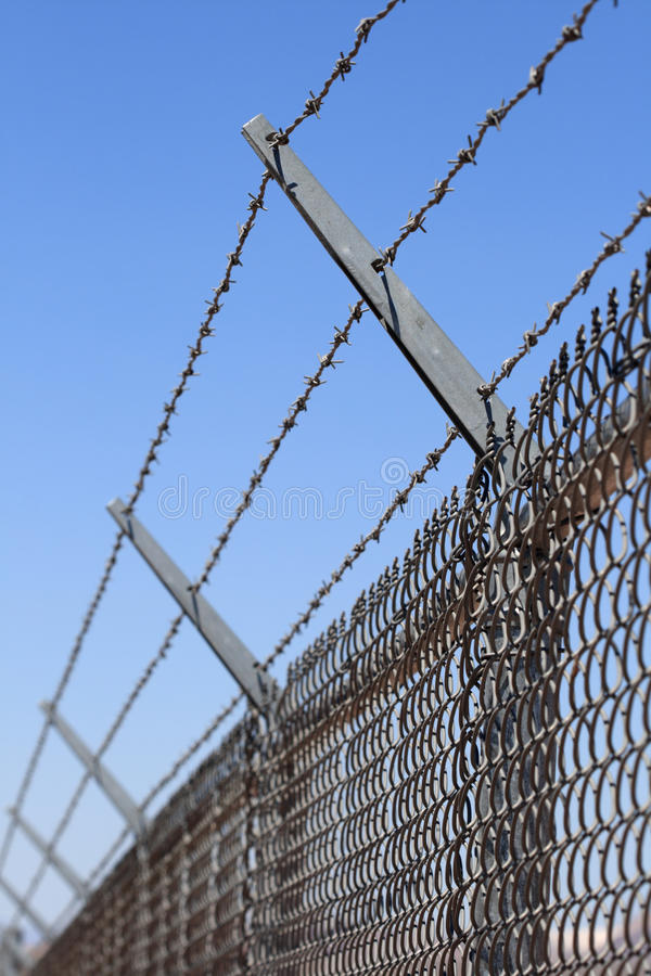 Security fence. Vertical image of a chain link security fence topped with three strands of barbed wire stock photography