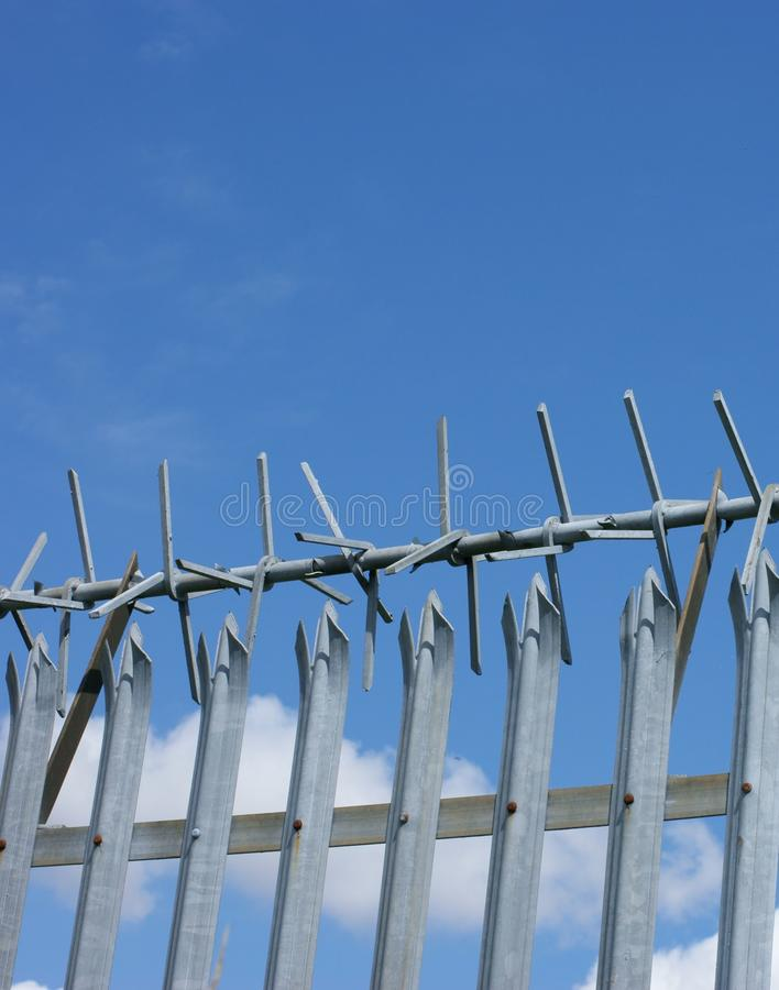 Security fence. Metal security fence with anti-climb top against blue sky stock images