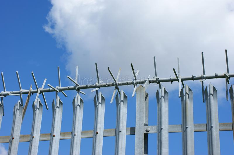 Security fence. Metal security fence with anti-climb top against blue sky royalty free stock photo