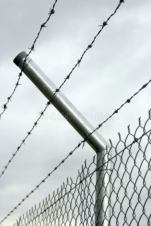 Security fence. Huge scared security fence with grey sky stock images