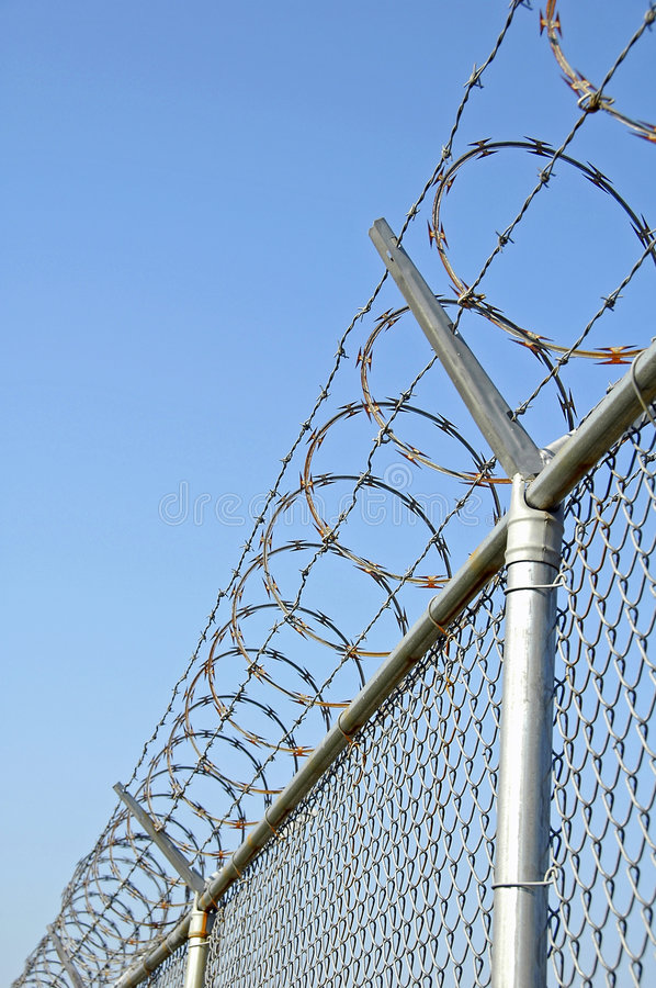 Security Fence. Chain link Security fence with razor wire stock images