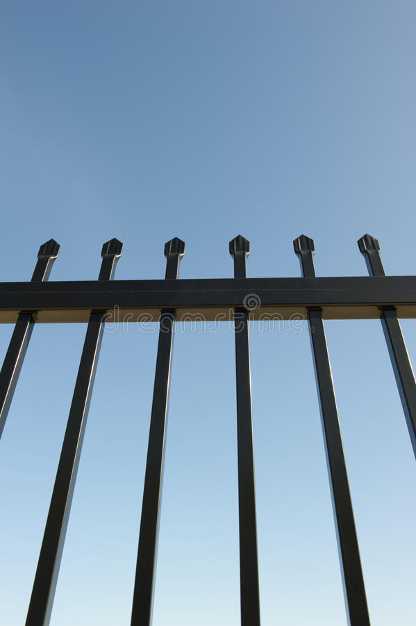 Security Fence around Industrial Property. Upward view of a metal security fence around an industrial property with spikes on top and a clear blue sky in the stock photos