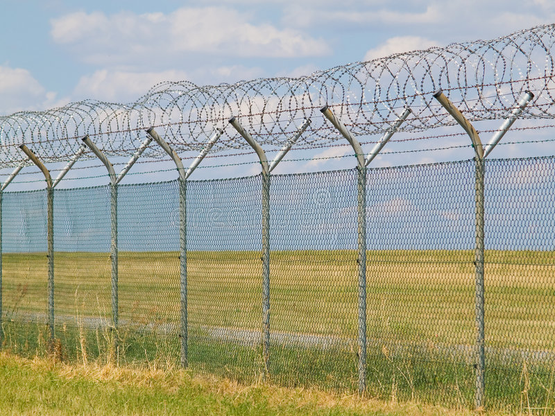 Security fence with barbedwire. Security fence with barbed wire and blue sky in background stock photography