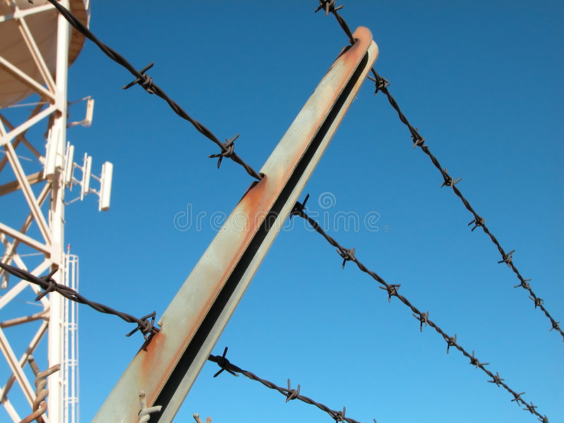 Security Fence with Water Tower. A section of security fence topped with barbwire such as would be used to guard the border or protect a sensitive site stock photo