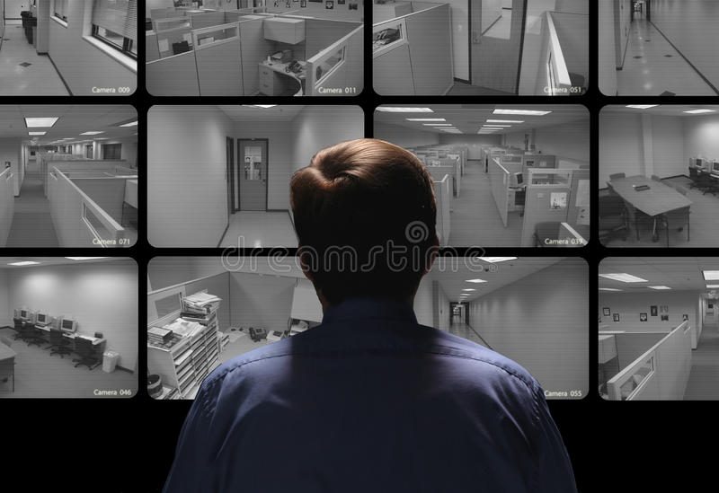 Security guard conducting surveillance by watching several security monitors royalty free stock images