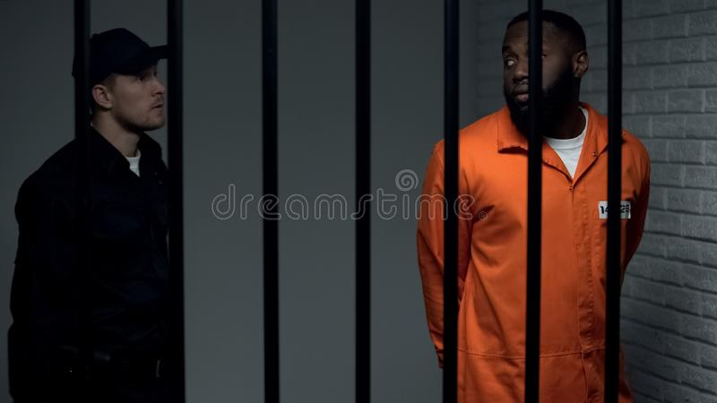 Security guard convoying afro american criminal, prison rules and regulations royalty free stock photos