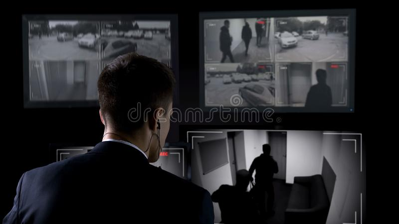 Security guard in earphones watching robbery attempt on surveillance cameras. Stock photo royalty free stock images