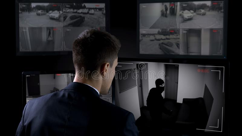 Security guard in front CCTV footage watching bank robbery, safety and guarding. Stock photo royalty free stock image