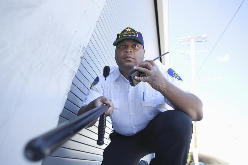 Security Guard Investigates With Walkie Talkie. Low angle view of a security guard communicating through walkie talkie while holding a baton stock images