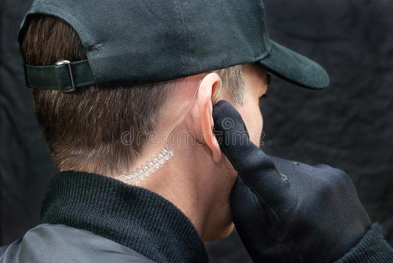 Security Guard Listens To Earpiece, Over Shoulder royalty free stock photo