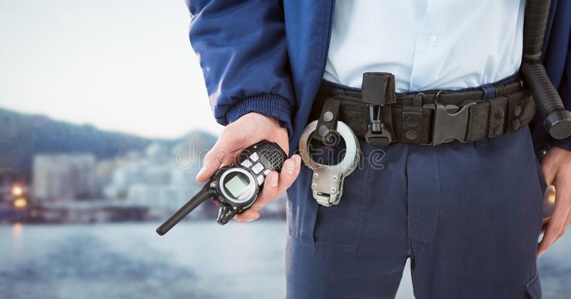 Security guard lower body with walkie talkie against blurry skyline. Digital composite of Security guard lower body with walkie talkie against blurry skyline stock image