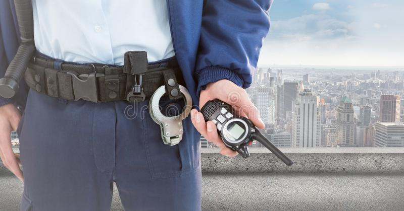 Security guard lower body with walkie talkie against skyline. Digital composite of Security guard lower body with walkie talkie against skyline stock photo