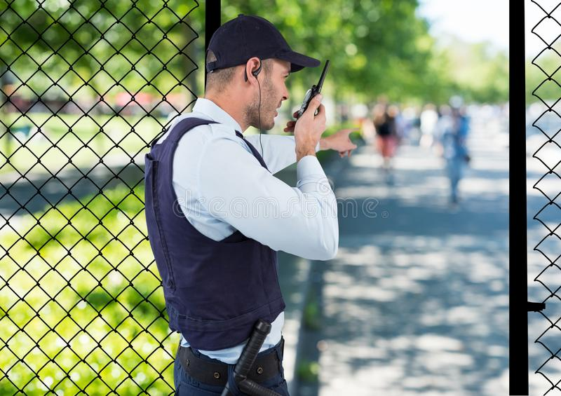 security guard of the park spiking with the walkie-talkie and point to something. stock photography